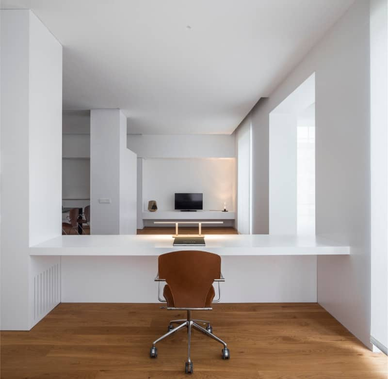 A brown office chair sits at a built-in white desk in this home office sporting a minimalist look.