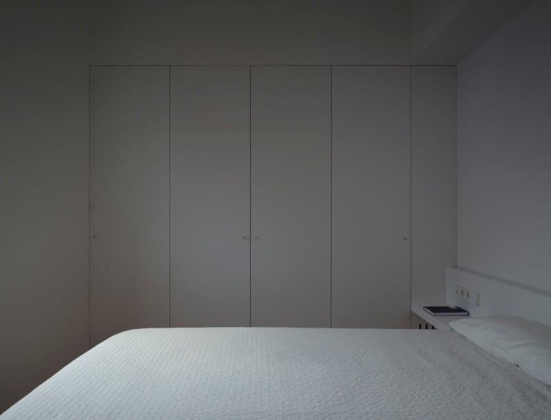 Minimalist tranquil guest bedroom in all-white with full size built-in cabinets.
