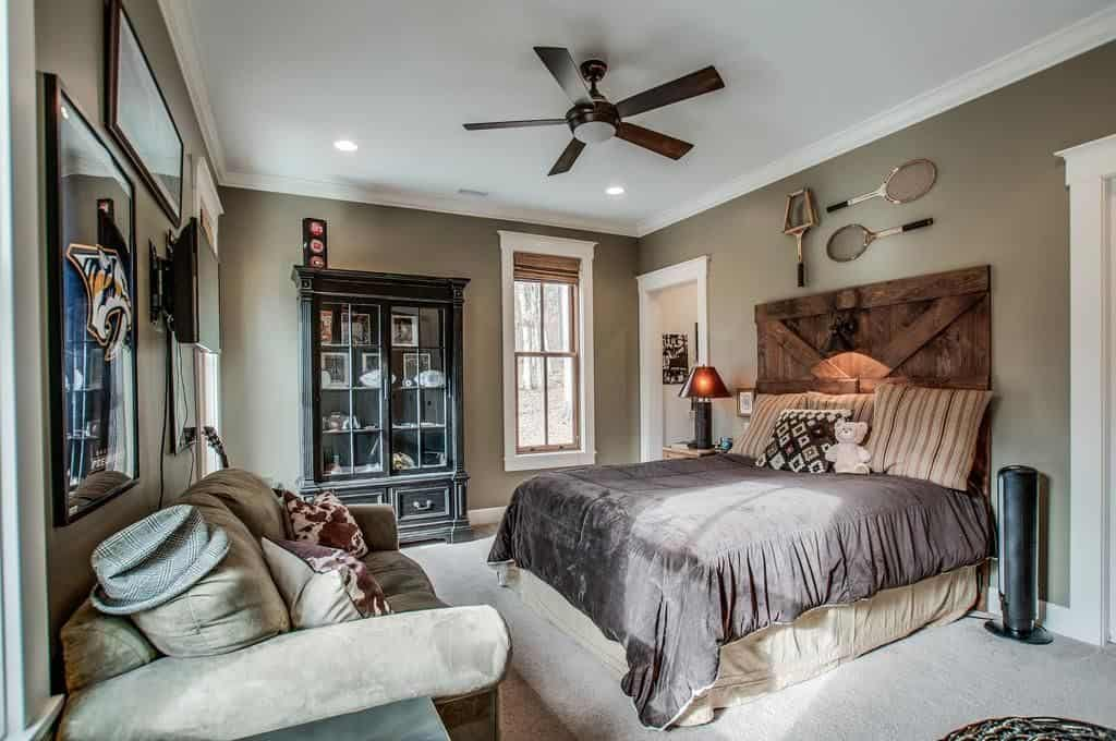 Sports-themed bedroom from Miley Cyrus' home for the guests with mocha-hued walls, carpeted floors and rustic furniture.