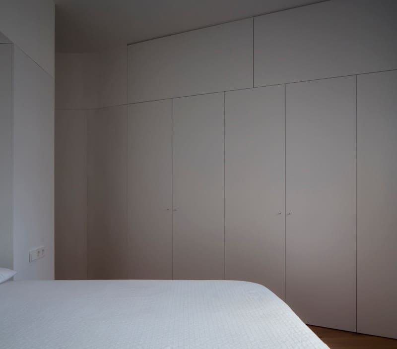 Minimalist guest bedroom in all-white with full size built-in cabinets and dark wood floor.