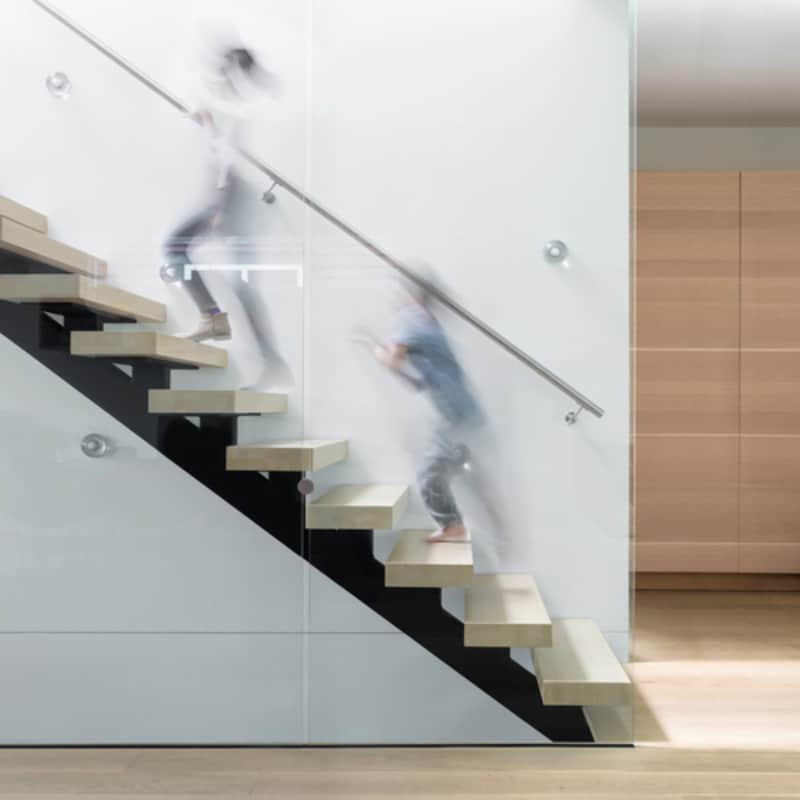 Mono black stringer staircase with light wood treads and floor to ceiling glass balustrade for added safety.
