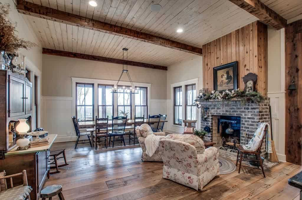 Cozy dining area features a brick fireplace accompanied by floral armchairs. It has a rectangular dining table by the glazed windows surrounded with black and wooden chairs.