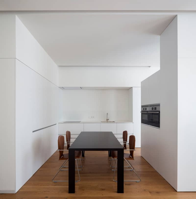 Minimalist kitchen with white walls and cabinets, a pair of stainless steel oven and a black center table with four brown chairs over a hardwood flooring.