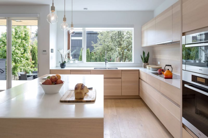 Light wood cabinets add a warm tone on this lovely L-shaped kitchen. Three clear glass globe pendant lights are hung from a white ceiling over a huge breakfast island.