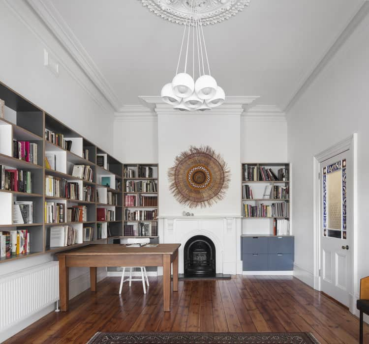 A gorgeous white home office decorated with a sunburst tapestry mounted above the fireplace. It is illuminated by white round pendants that hung from the ornate ceiling.