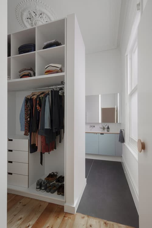 Small white walk-in closet with hardwood flooring.