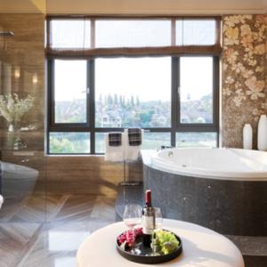 Brown Bathroom with Large Window, bath tub and dark flooring