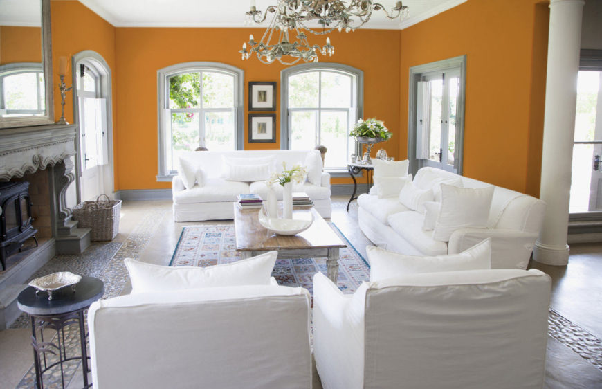 This spacious open terra cotta orange living room merges the Victorian with a contemporary theme. The vintage chandelier, intricately patterned fireplace, stone floors, wrought iron corner tables, vases, antique rug, and candelabra gives off the vibes from a bygone era, while the cozy all-white sofa, fluffed-up pillows, and polished wood center table are truly inviting.