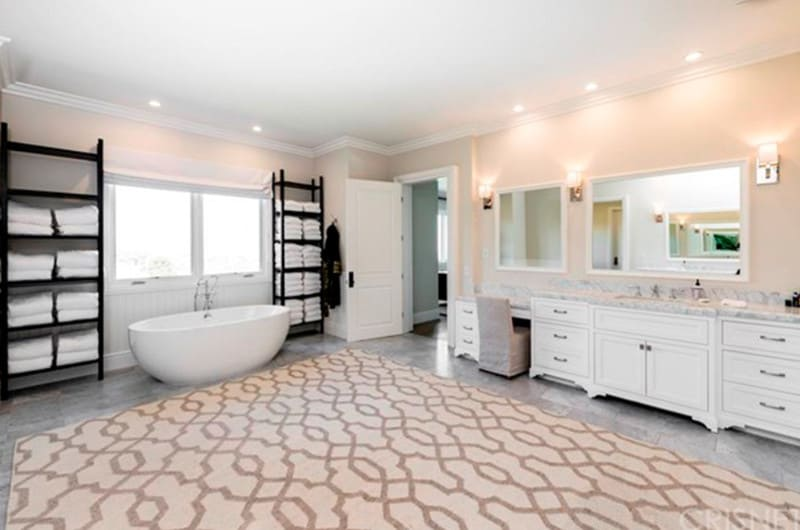 Spacious master bathroom with gray tiles flooring topped by a large rug. There's a freestanding tub, a powder desk and a sink counter lighted by wall lights.