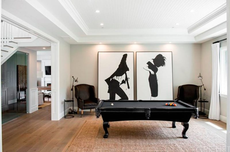 A black pool table sits on a jute rug accompanied by leather wingback chairs in this open game room decorated with large black and white wall arts.
