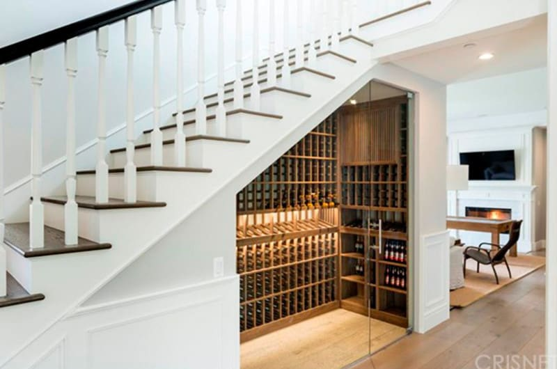 Small wood wine cellar enclosed with a glass door beneath a two-tone staircase. It's a great idea for maximizing space.