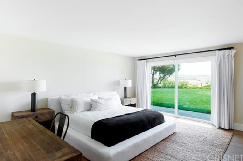 A minimalist guest suite simplified with a carpeted bed space, large window overlooking the stunning view from the yard, two side lamps and a study table.