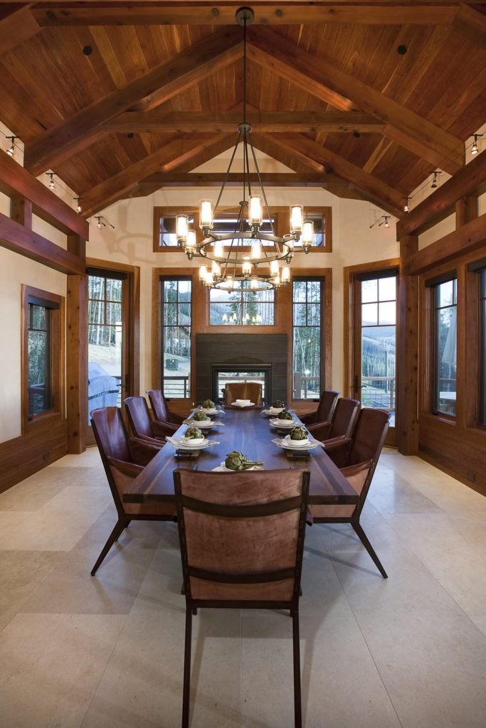 A dining room offering a long dining table set under the wooden vaulted ceiling with exposed beams lighted by fancy ceiling lights.