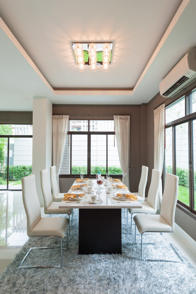 Modern dining room featuring a modern dining table and chairs set on top of a thick gray area rug. The table set is situated under the tray ceiling lighted by fancy ceiling lighting.