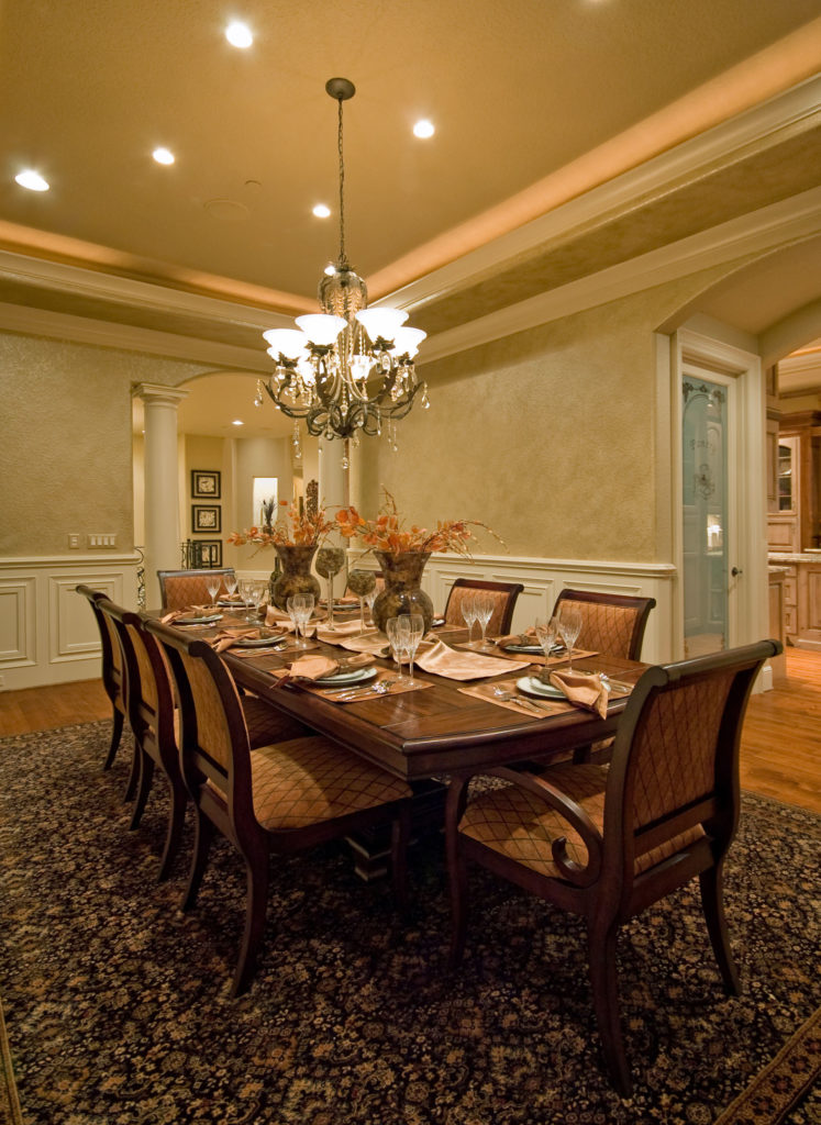 A focused shot at this dining room's elegant dining table and chairs set on top of a large area rug covering the hardwood flooring. The table set is lighted by a gorgeous chandelier.