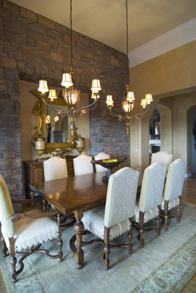 This dining room offers a classy dining table and chairs set lighted by two gorgeous chandeliers hanging from the tall ceiling.