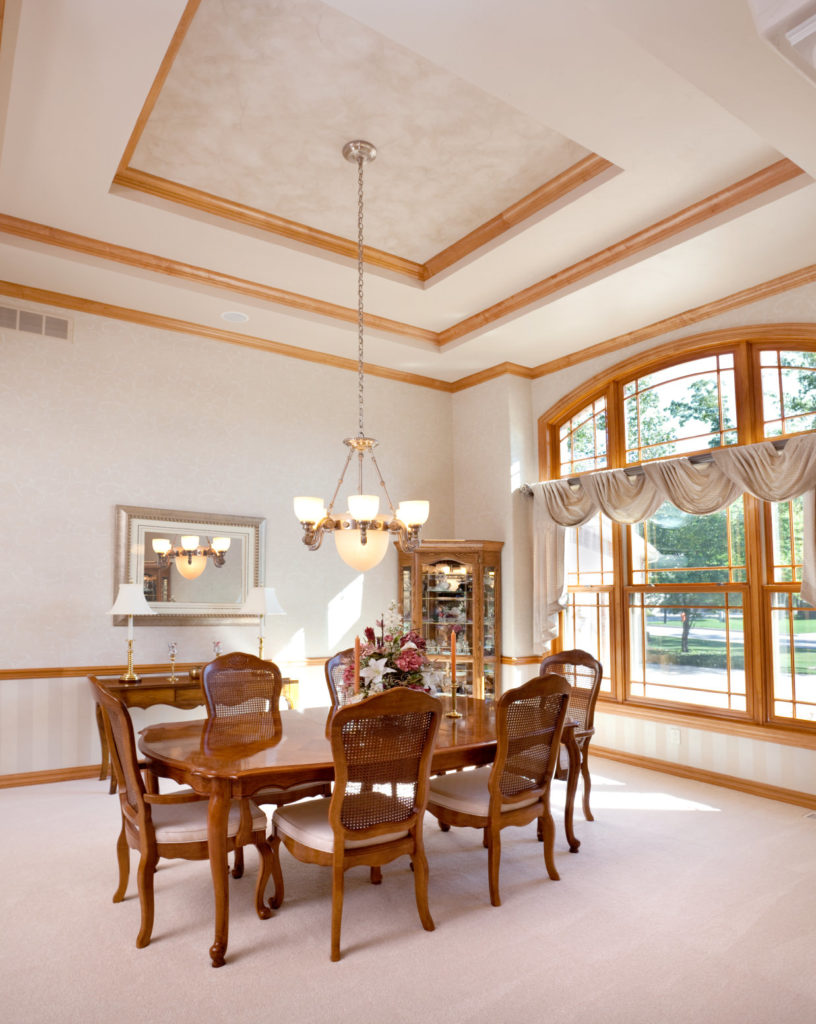 A spacious dining space featuring a stunning tray ceiling and fine carpet flooring. The area offers a wooden dining table set lighted by a fancy ceiling light.
