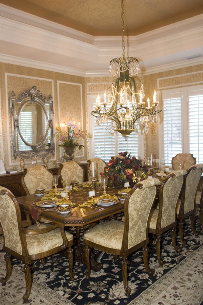 A focused look at this dining room's luxurious dining table and chairs set lighted by a glamorous chandelier and is surrounded by elegant walls and tray ceiling.