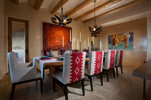 A spacious dining room boasting a dining table for 10 lighted by gorgeous ceiling lights hanging from the custom ceiling with beams.