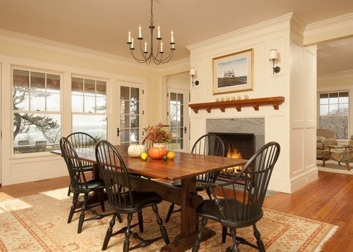 A focused look at this wooden dining table set on top of a classy area rug. The room also features a fireplace on the side.