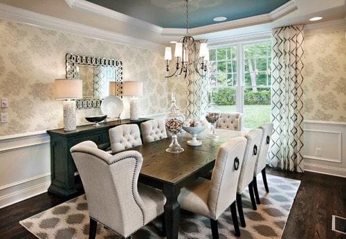 Dining room surrounded by elegantly decorated walls and has a stunning tray ceiling. It features a wooden dining table paired with classy chairs on top of an area rug covering the hardwood flooring.