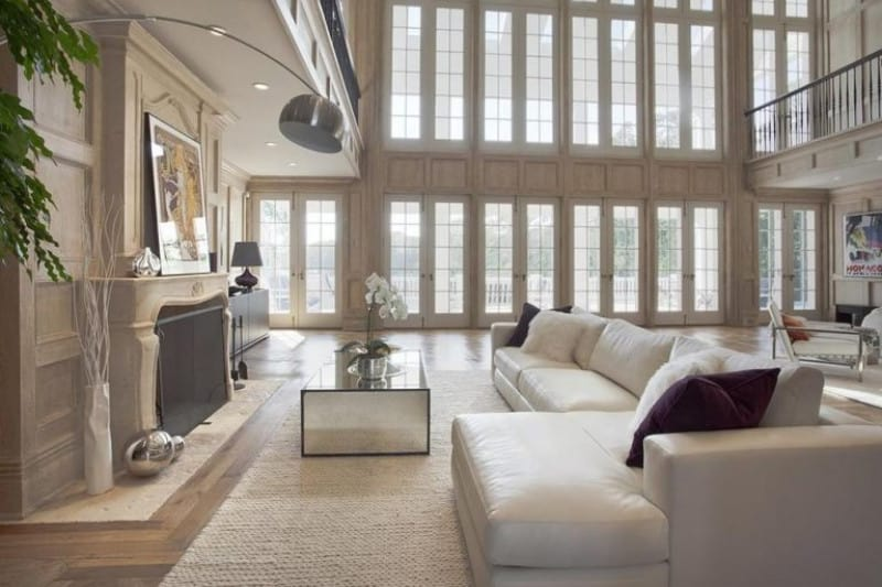 Another look of the couple's formal living room focusing on the white sofa set with white rug and recessed ceiling lights in front of the fireplace.
