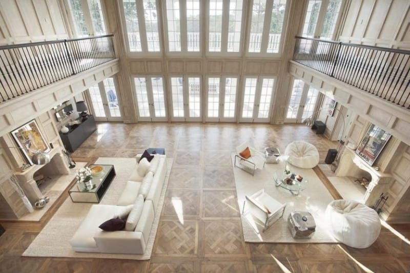 This view of this formal living room is taken from the mansion's second floor, overlooking the white seats and two fireplaces together with the stylish flooring.