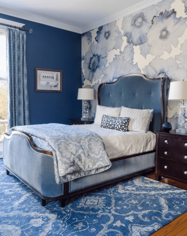 Clad in floral wallpaper, this blue bedroom offers a tufted wingback chair that sits on a patterned area rug. It is accompanied by dark wood nightstands and glass table lamps.