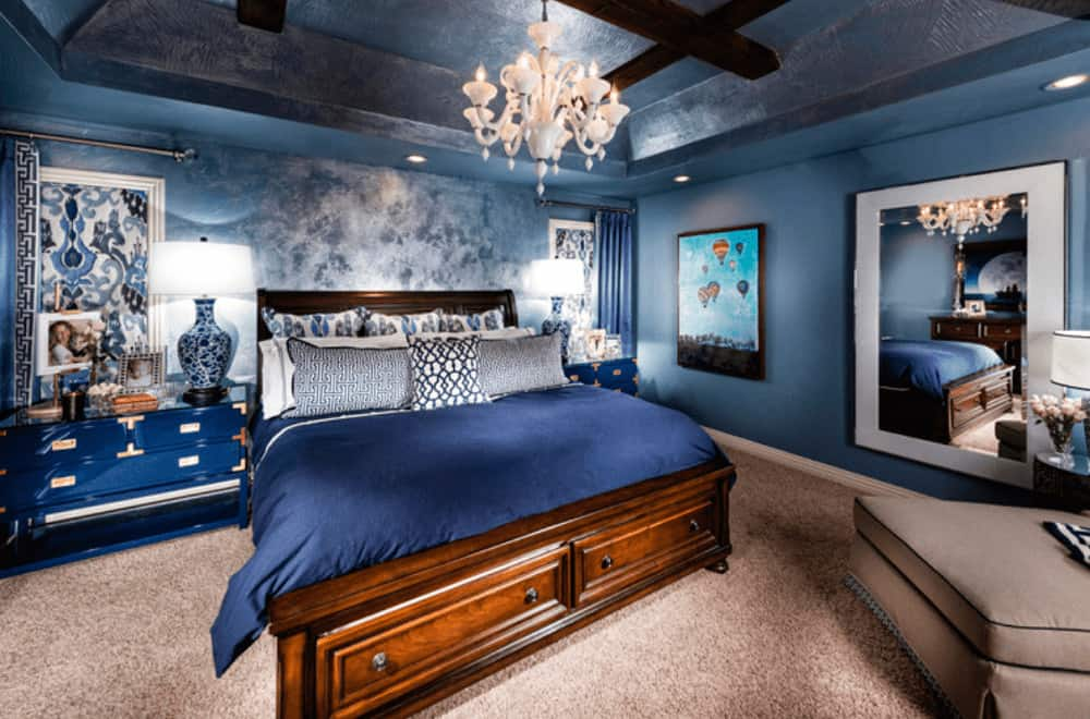 A gorgeous white chandelier illuminates this primary bedroom boasting a wooden bed and ceramic table lamps that sit on the blue nightstands.