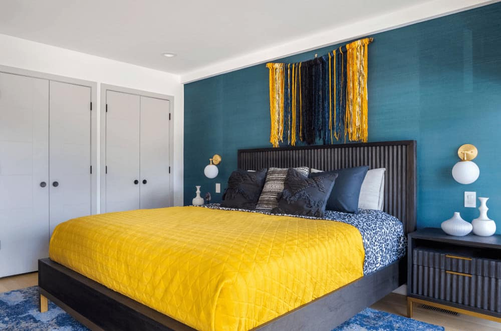 Contemporary bedroom decorated with a gorgeous yarn tapestry that hung above the wooden bed dressed in yellow bedding. It has globe sconces and white vases that sit on dark wood nightstands.