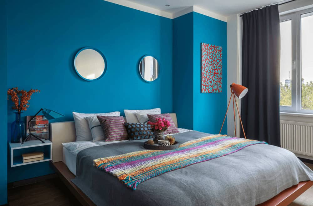 Blue bedroom showcases a lovely artwork and multi-color knitted throw that lays on the cozy bed. It includes round mirrors and floating shelf topped with stylish lamp and translucent vase.