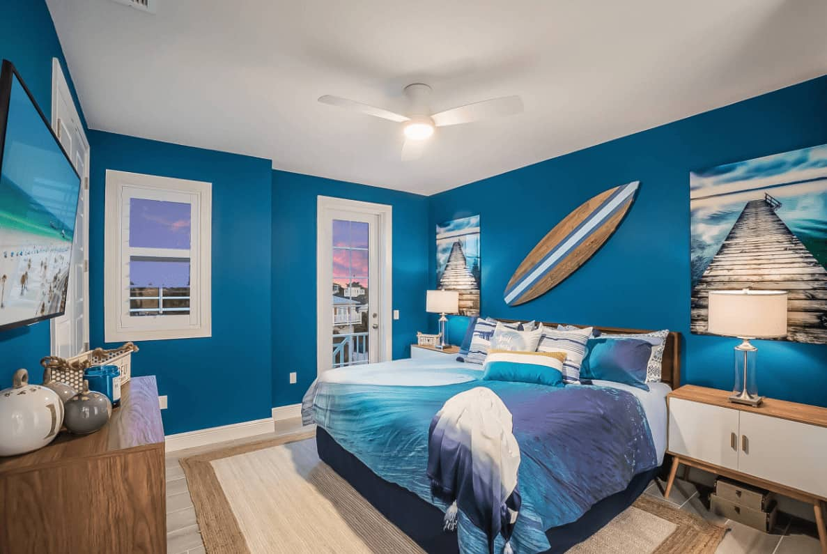 Beach style bedroom decorated with gorgeous artworks and a decorative surfboard mounted above the comfy bed. It has a jute area rug and wooden nightstands topped with glass table lamps.