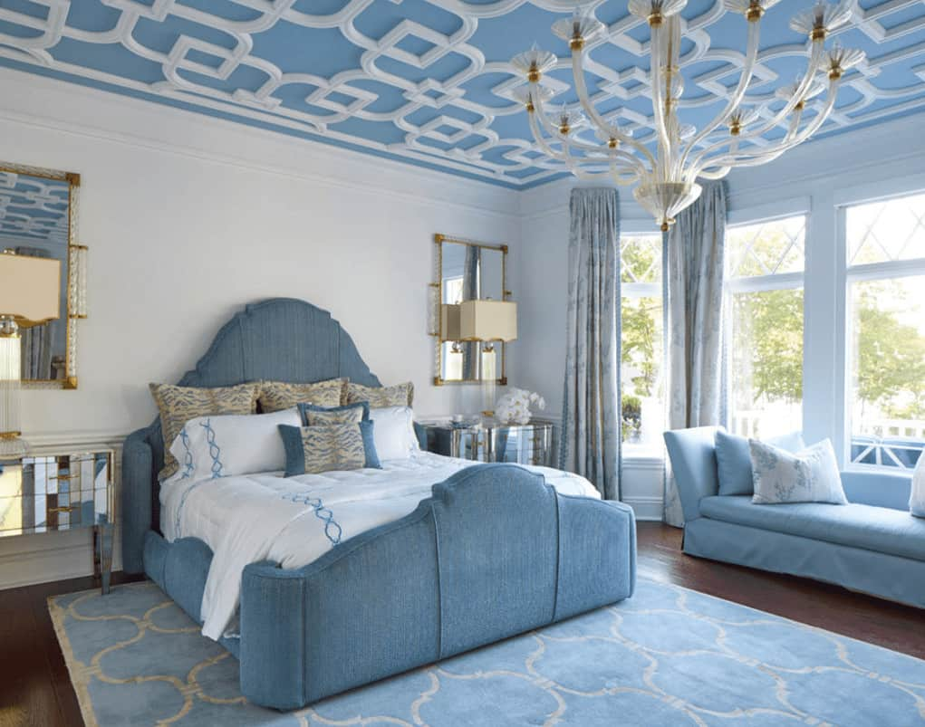Stylish bedroom with mirrored nightstands and a blue upholstered bed accompanied by a skirted seat. It is illuminated by an oversized white chandelier that hung from the ornate ceiling.