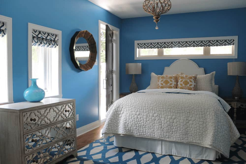 Fabulous bedroom with a charming chandelier and round mirror mounted on the blue wall. It includes a skirted bed and mirrored drawer chest topped with a blue vase.