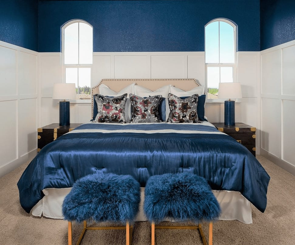 Transitional bedroom offers a gorgeous bed surrounded by wainscoted walls and arched windows. It includes faux fur stools and blue table lamps that sit on dark wood nightstands.