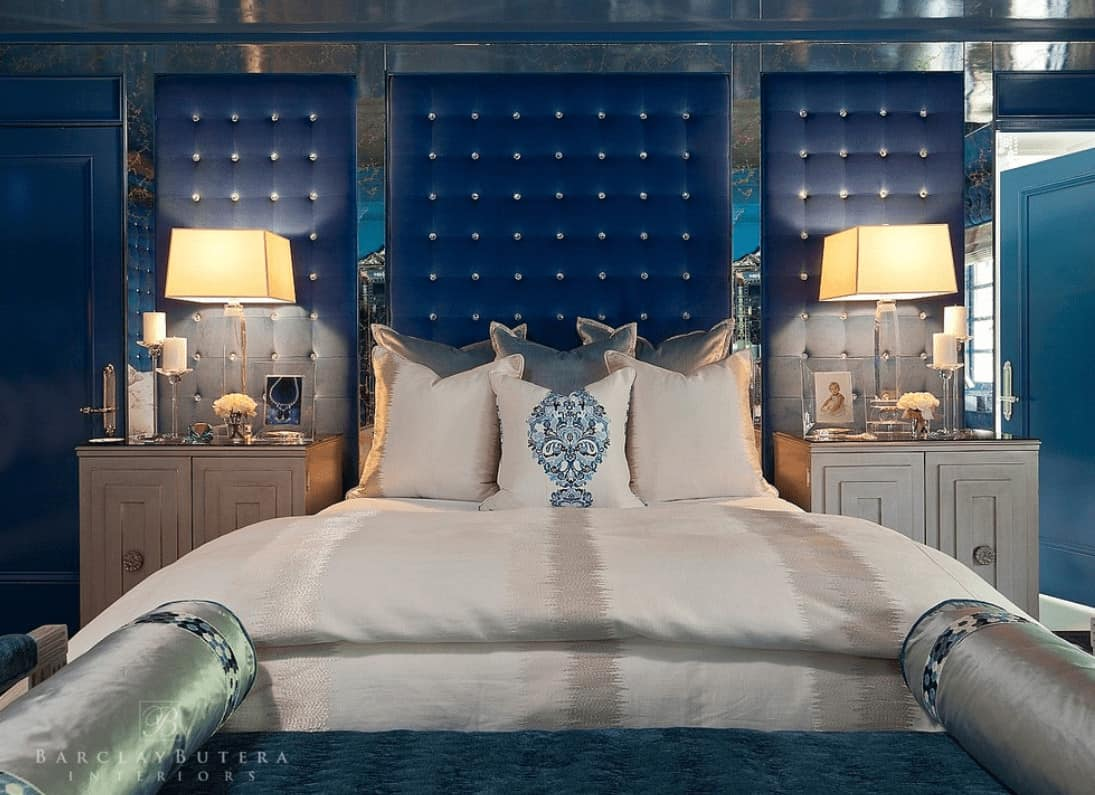 Luxury primary bedroom with a classy bed and wooden nightstands placed against the mirrored wall that's fitted with blue tufted panels.