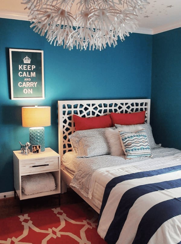 A blue table lamp sits on the light wood nightstand in this bedroom with a framed artwork and white ornate bed over a red patterned rug.