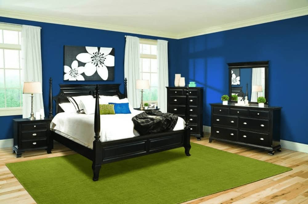 A vibrant green area rug adds a striking accent in this blue bedroom with black furniture and a lovely floral wall art mounted in between the white framed windows.