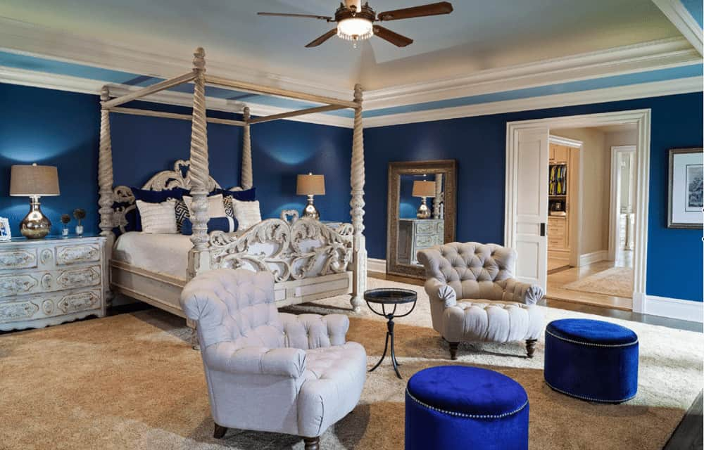 Beige tufted armchairs paired with blue velvet ottomans sit in front of the four poster bed complementing the distressed nightstands topped with chrome table lamps.