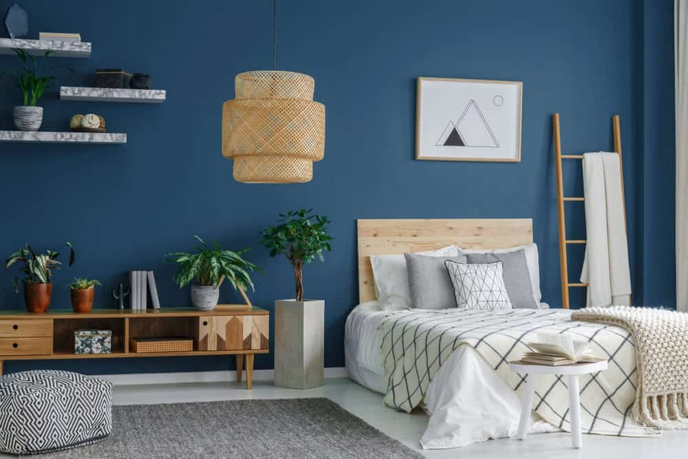 Fresh bedroom offers a wicker chandelier and light wood bed with a ladder on its side that serves as a rack. It includes marble floating shelves and a patterned ottoman that sits on the gray area rug.