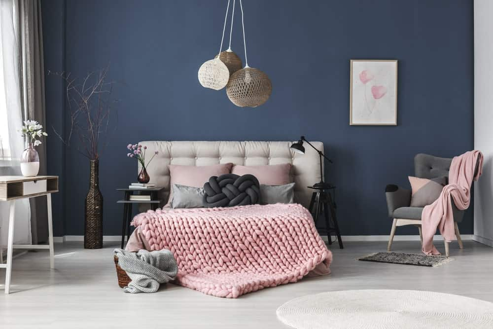 Navy blue bedroom accented with light pink bedding, artwork and throw blanket that lays on the green tufted armchair. It is decorated with lovely flower vases and boho <a class=