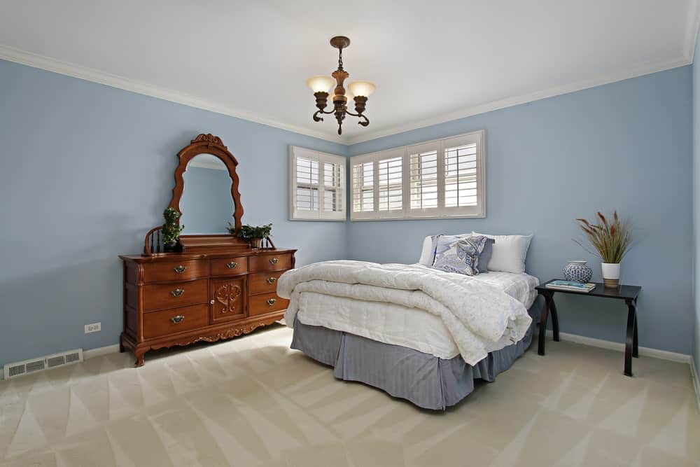 A vintage chandelier hangs over the skirted bed that's accompanied by a black nightstand and wooden dresser placed against the muted blue walls.