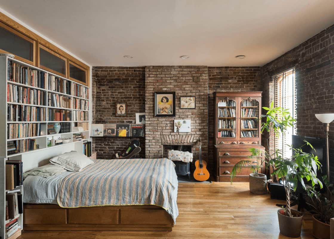 Green potted plants create a refreshing ambiance in this primary bedroom showcasing built-in bookshelves and a fireplace concealed in the brick walls.