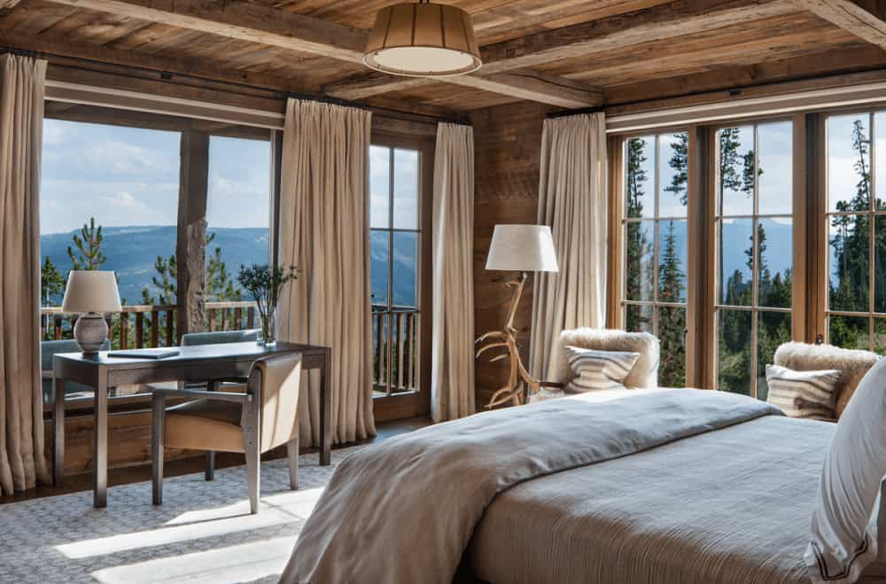 Brown primary bedroom surrounded with floor to ceiling windows that overlook the stunning mountain. It has a wooden desk and a cozy bed illuminated by a pendant light.