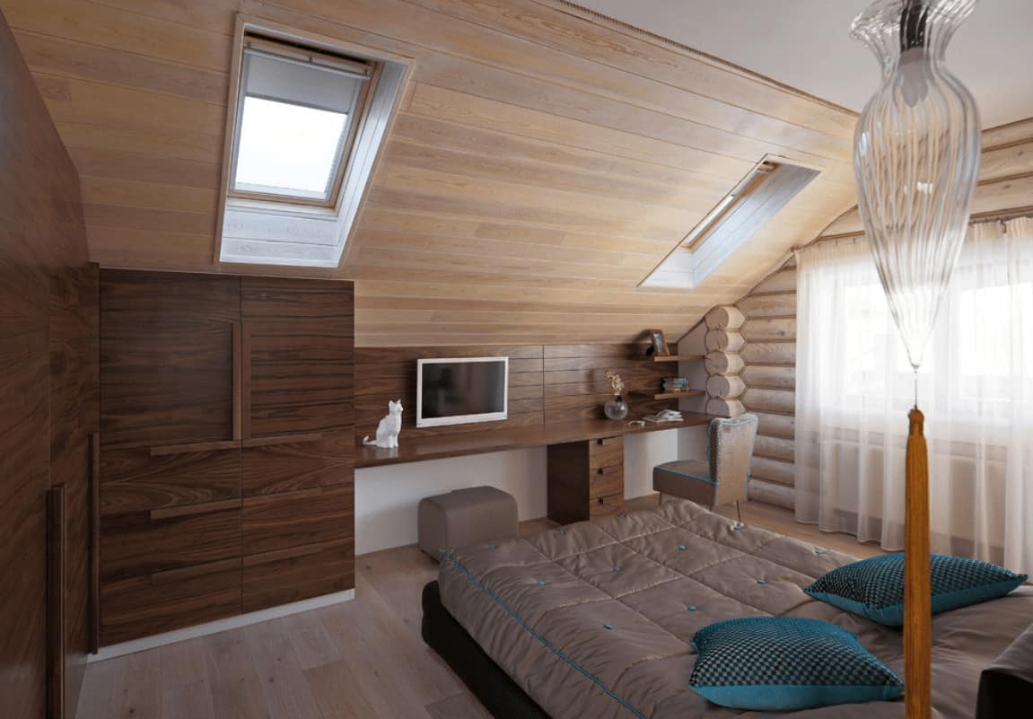 A cozy bed faces the built-in desk in this primary bedroom with floor to ceiling cabinets and a vaulted wall clad in light wood planks and fitted with skylight windows.