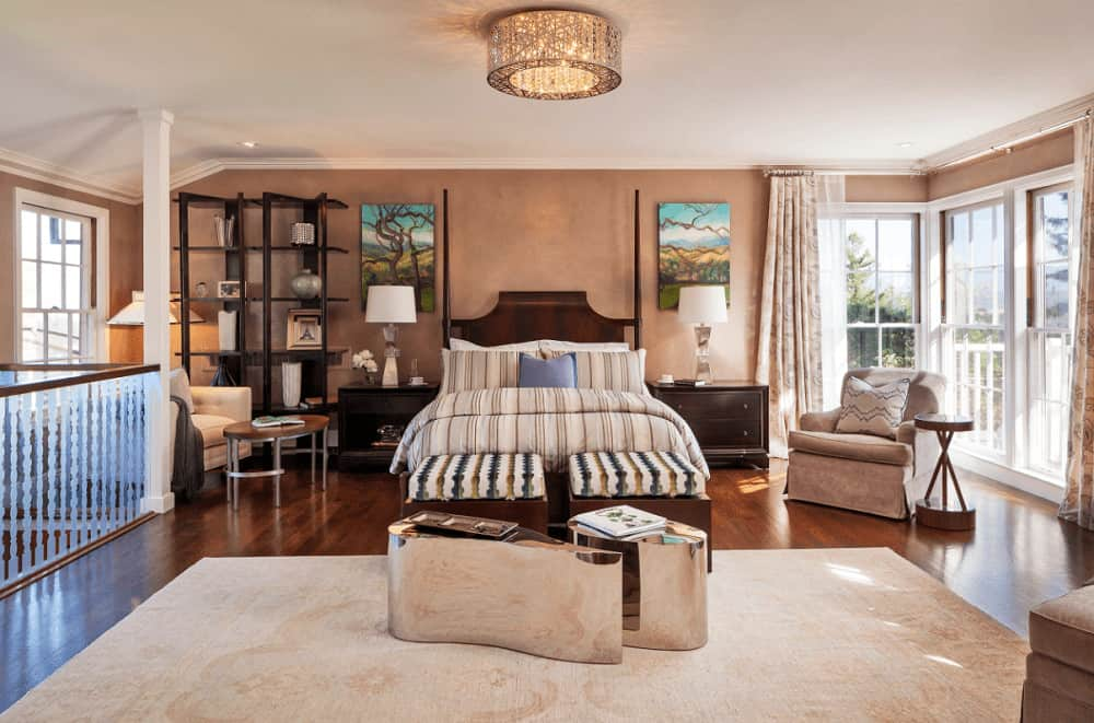 This primary bedroom is decorated with a fancy flush mount light and lovely tree wall arts that hung over the dark wood nightstands. It has beige seats and a wooden bed with striped ottoman and stylish mirrored tables on its end.