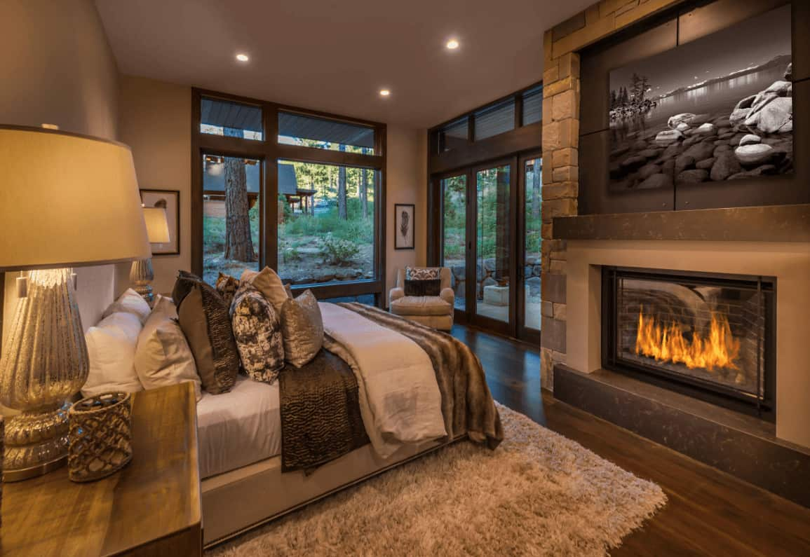 The warm primary bedroom boasts a comfy bed and a fireplace with a landscape canvas on top. It has full height glazing and hardwood flooring topped by a gray shaggy rug.