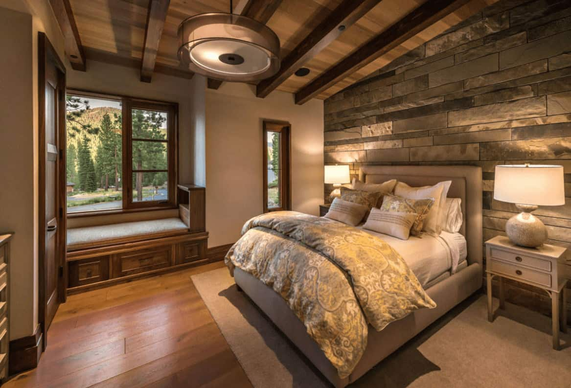 A stone accent wall adds texture in this primary bedroom with a window seat nook and beige upholstered bed lighted by a pair of table lamps along with a drum pendant light.