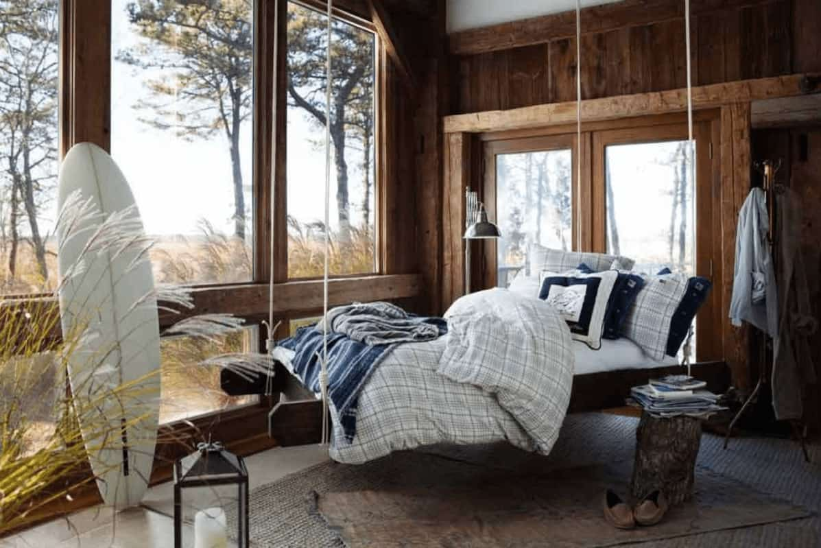 Natural light flows in through the glass paneled windows in this rustic bedroom offering a hanging bed and a stump coffee table that sits on layered rugs.