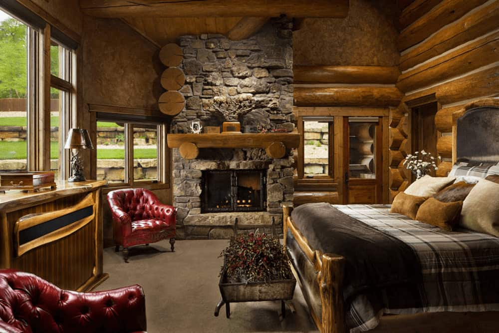 Fluffy earthy pillows lay on the cozy bed in this primary bedroom boasting red chesterfield chairs and a stone fireplace lined with a wooden mantel.